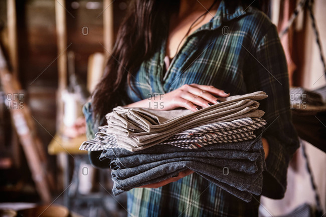 Close of a female store assistant holding handmade kitchen fabrics