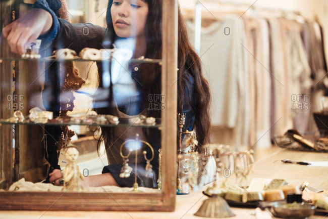Female store assistant on rearranging jewelry cabin at clothing boutique store