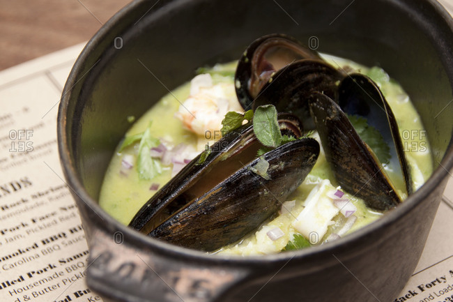 Soup with mussels served in saucepan