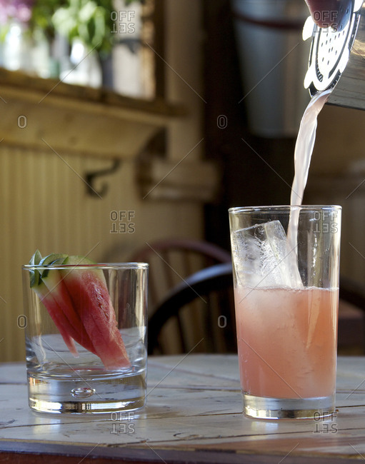 Pouring watermelon cocktail into tall glass