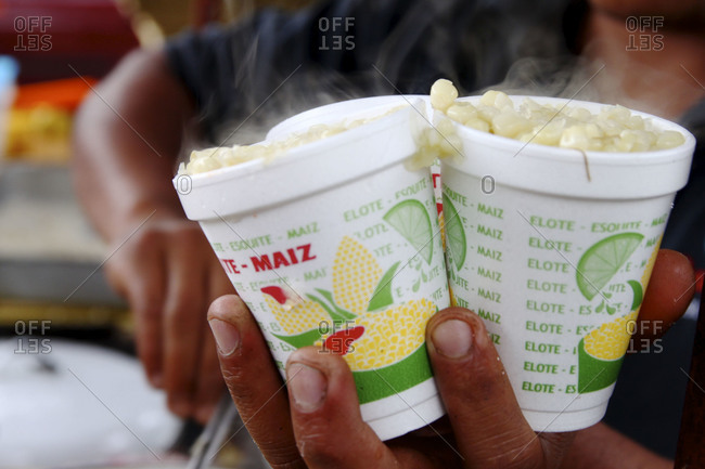Street vendor holding two cups of mexican corn salad