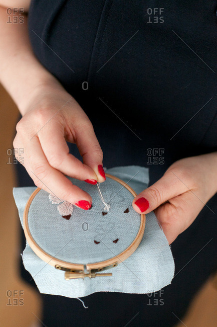 Hands of woman embroidering - Offset