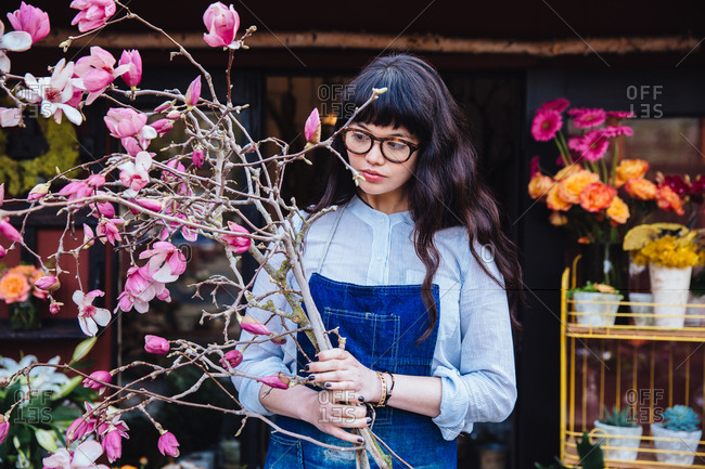 Female florist with bundle of flowering tree branches