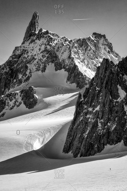 Man skis to the foot of Aiguilles Marbrees from Col des Flambeaux,  Mont Blanc range, Chamonix