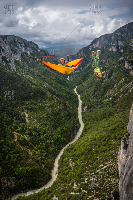 Verdon Gorge, France - May 6, 2013: Mich Kemeter relaxes while Armin Holzer bat hangs on a highline far above the ground in the Verdon Gorges