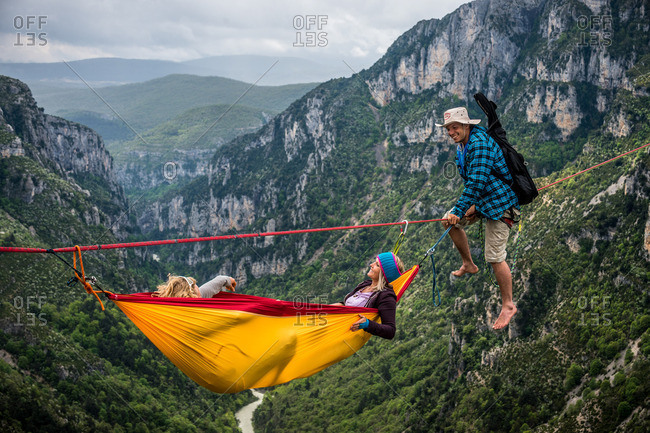 Verdon Gorge, France - May 6, 2013: Niccolo Zarattini plays music for Mich Kemeter and girlfriend Karine carrying guitar on a highline towards his friends in a hammock far above the Verdon river