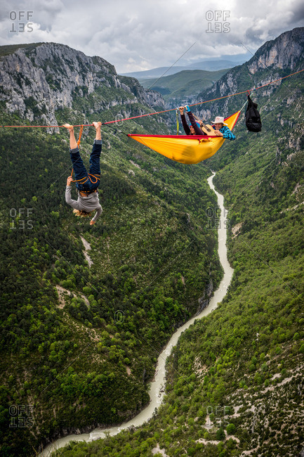 Verdon Gorge, France - May 6, 2013: Mich Kemeter hanging on a highline while friends relax in a hammock far above the Verdon river