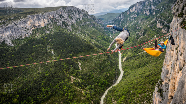 Verdon Gorge, France - May 6, 2013: Mich Kemeter highlining while friends relax in a hammock far above the Verdon river