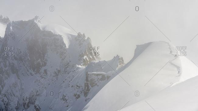 Skiers climb back up one of the domes on the Midi-Plan ridge, Chamonix, France