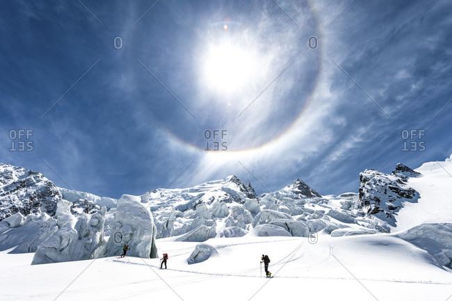 A sun halo above skiers climbing La Jonction, Chamonix, France