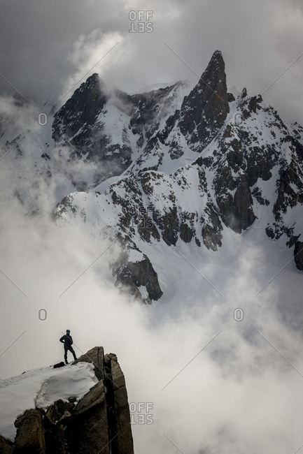 Mountain climber standing on cliff edge in French Alps