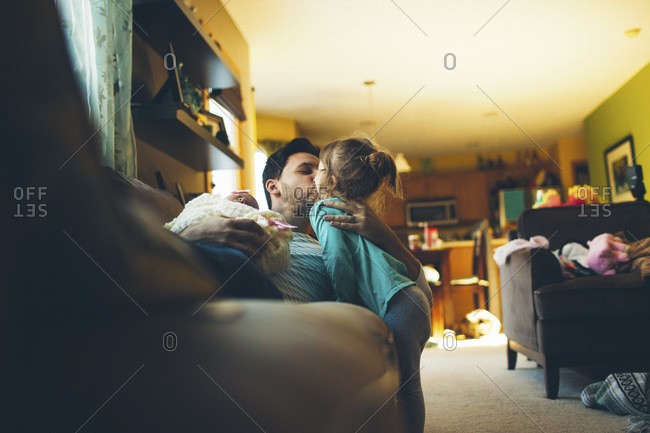 Man kissing his young daughter at home