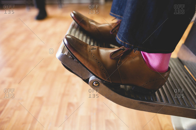 Feet of a man wearing pink socks and elegant shoes