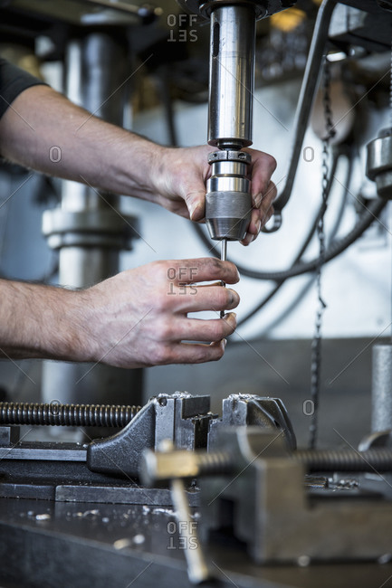 Man operating drill machinery in metal shop