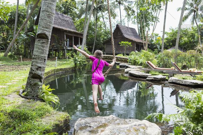 Caucasian girl swinging on rope in garden, Ubud, Bali, Indonesia