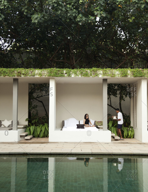 Galle, Sri Lanka - February 26, 2012: Guest relaxing in Ambalama (rest pavilion) by pool