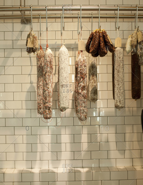 Sticks of salami and sausages hanging from hooks
