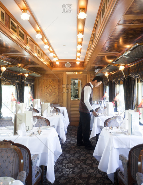 Feburary 9, 2012:  Waiter setting the table for lunch service on the Eastern & Oriental Express