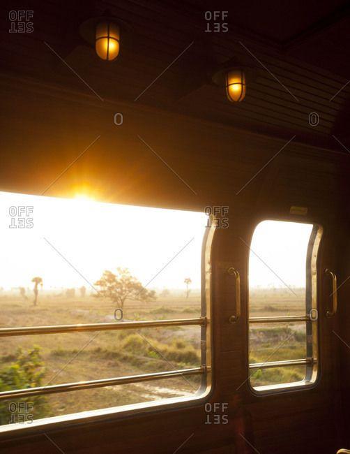 Sunset over a field viewed from a passenger car