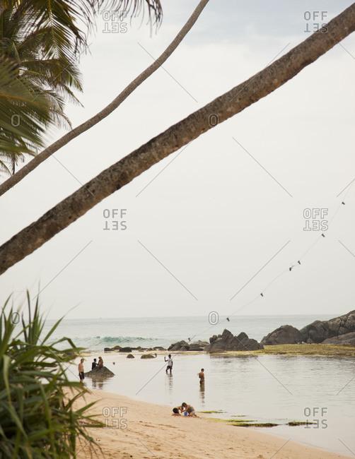 Unawatuna Beach, Sri Lanka - February 22, 2012: People at Unawatuna Beach