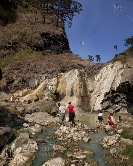 Lombok, Indonesia - August 14, 2011: Tourist wading in the hot spring on Mount Rinjani