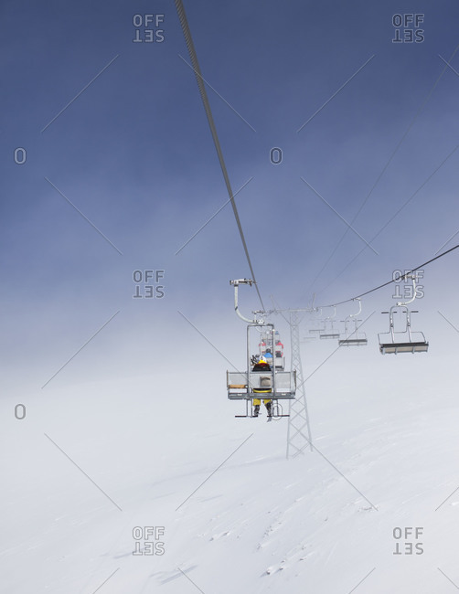 Ski lifts with skiers heading toward the peaks
