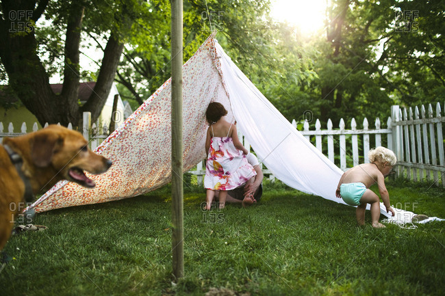 Two children and an adult make a tent out of sheets