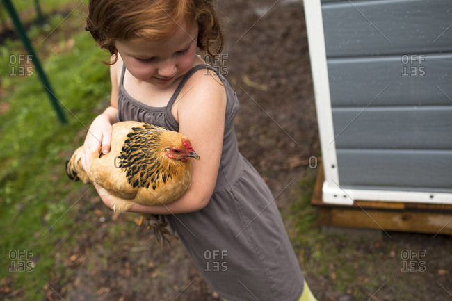 Cute girl holding a chicken in her arms