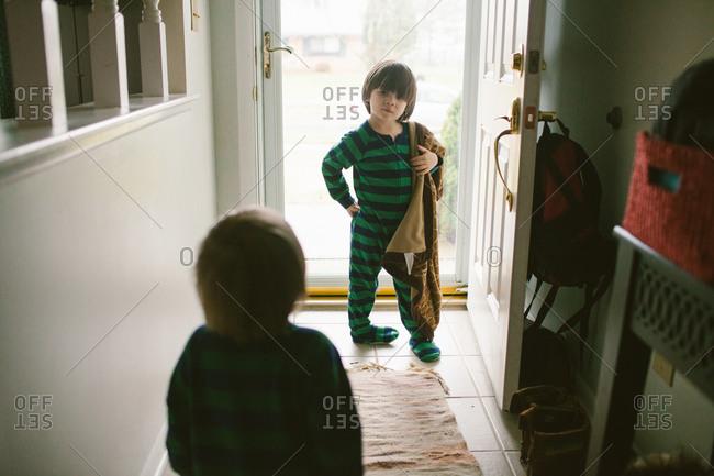Children in pajamas standing near the front door