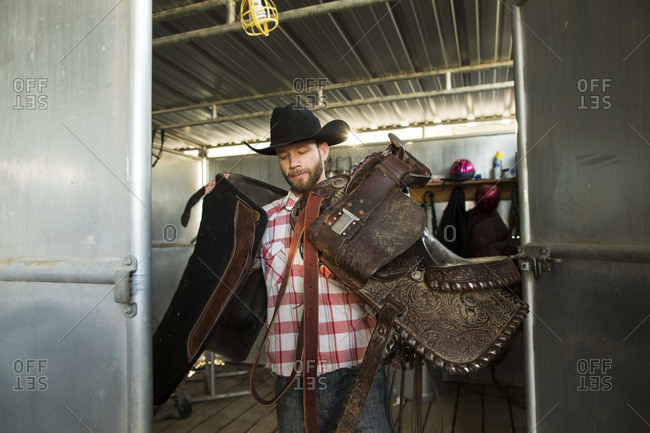 Man carrying cowboy accessories