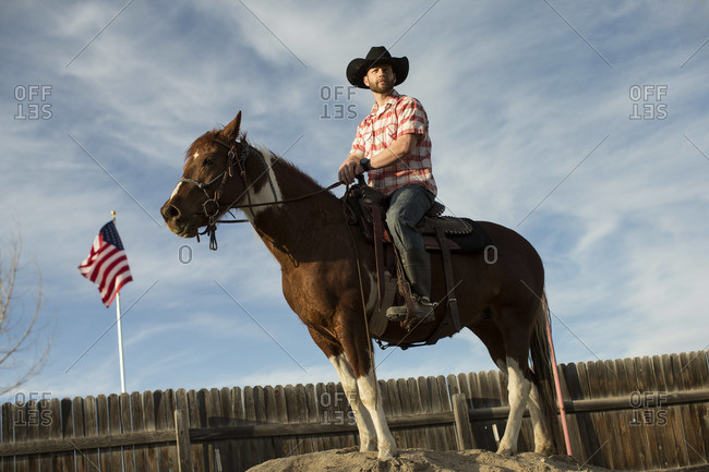 Cowboy sitting on horse on American ranch