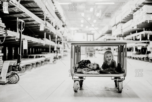 Two girls having fun on a warehouse store cart