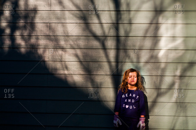 Young girl standing against a wooden exterior of a building