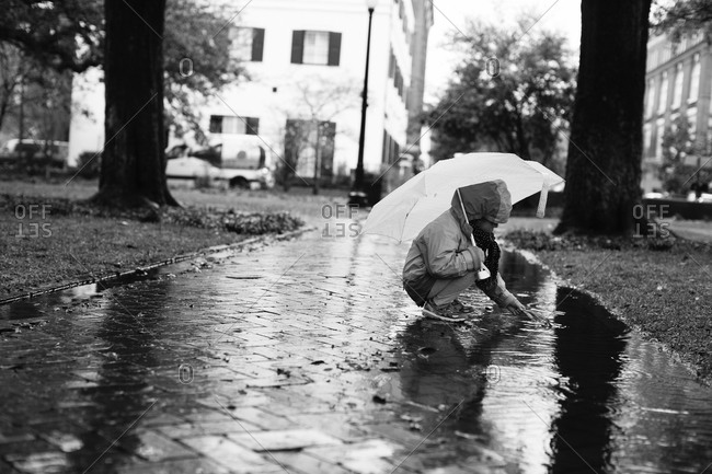 Young girl kneeling down while holding an umbrella picking a leaf from a puddle in the park
