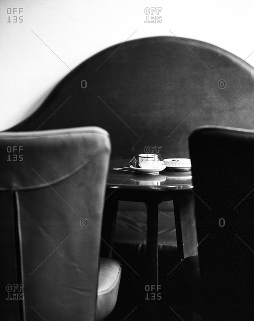 Elegant cafe interior with cup of espresso and mini tart