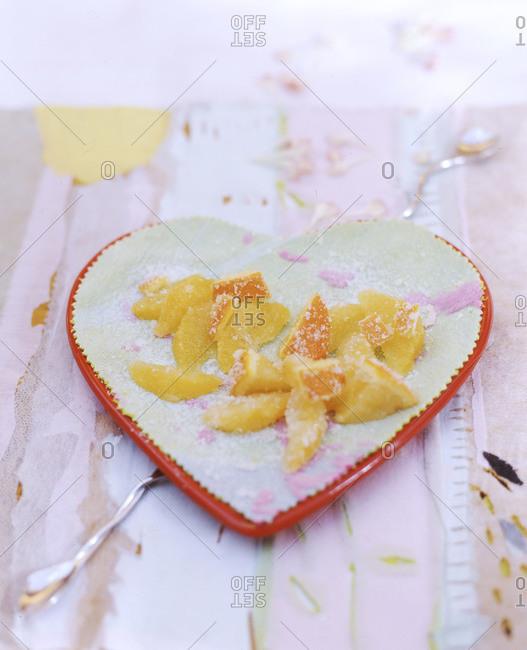 Candied orange on heart-shape plate