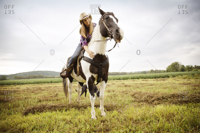 Young woman petting a horse