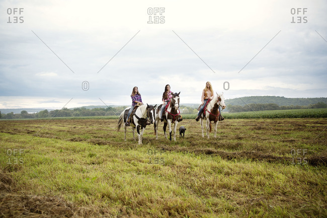 Women riding horses at a field