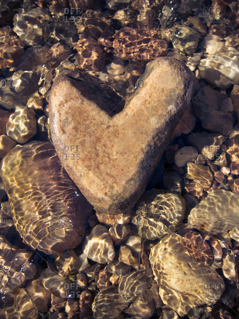 Heart-shape pebble in shallow water