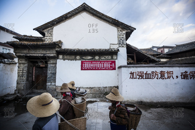 Dali, Yunnan, China - April 13, 2014: Farmers walk through a small village outside of Dali on their way to their farms.