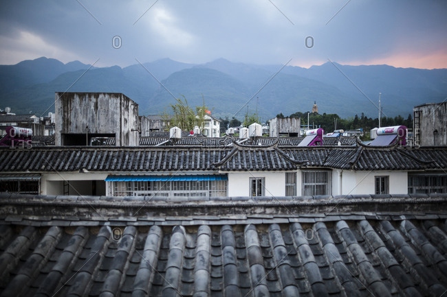 View showing rooftops of Chinese dwellings with Cangshan Mountains in the background, downtown Dali, China.