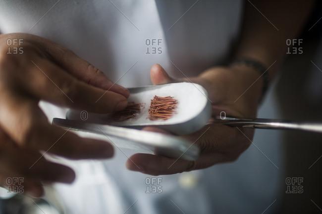 Doctor holding small acupuncture needles, Hanoi, Vietnam.