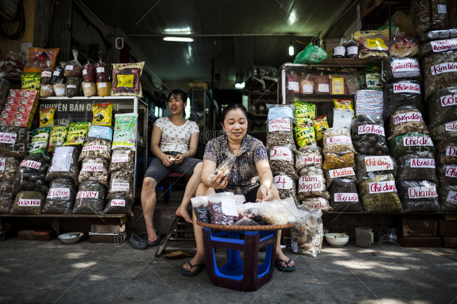 Lan Ong street in Hanoi's Old Quarter, Vietnam - September 16, 2013: A woman mixes dried medicinal herbs in front of her shop on Lan Ong street in Hanoi's Old Quarter, in northern Vietnam.
