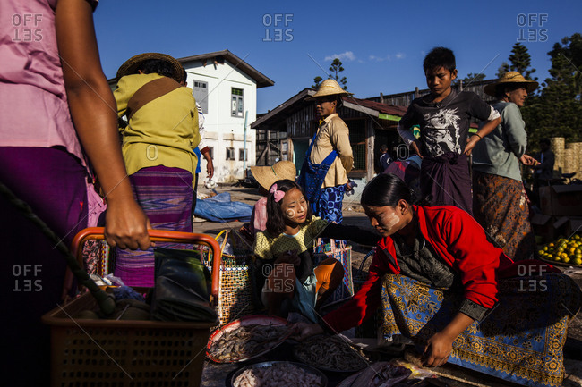 Shan State, Myanmar - October 21, 2012: Customers and sellers crowd in the street at a local market in Shan State, Myanmar.
