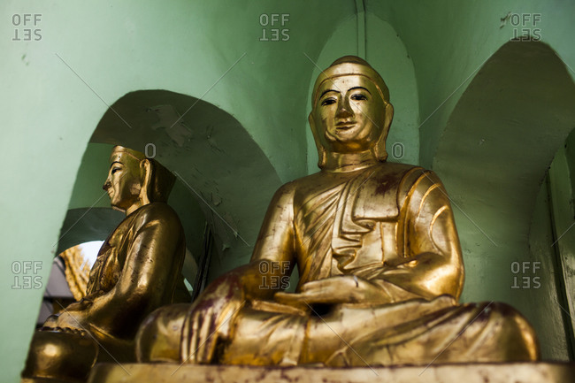 Buddha statues covered in gold at Shwedagon Pagoda in Yangon, Myanmar.