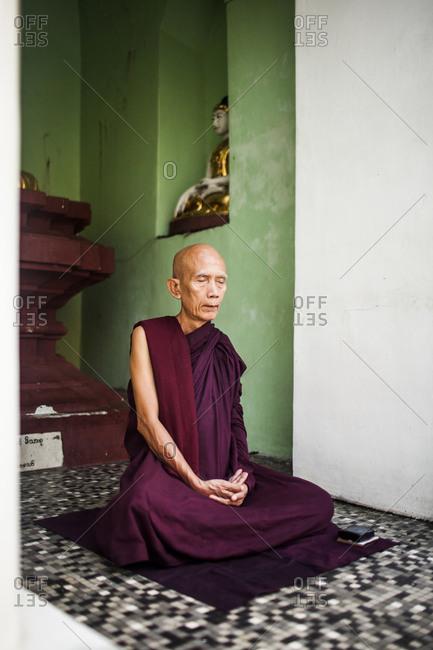 Shwedagon Pagoda, Yangon, Myanmar - October 7, 2013: An elder monk sits in silent prayer at Shwedagon Pagoda in Yangon, Myanmar.