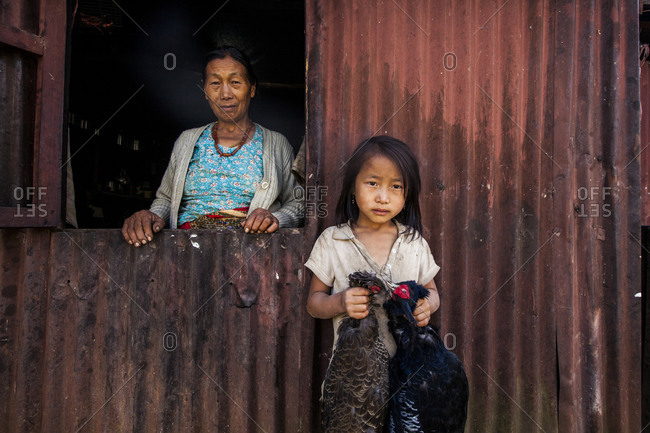 Angami village, Kohima, Nagaland, India - December 2, 2012: A grandmother and her granddaughter stand for a portrait outside of their home, Angami village outside of Kohima, Nagaland, India.