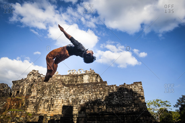 Shinta Mani hotel, Siem Reap, Cambodia - November 29, 2013: Phare Circus performer doing a back flip outside the Angkor Wat temple complex.