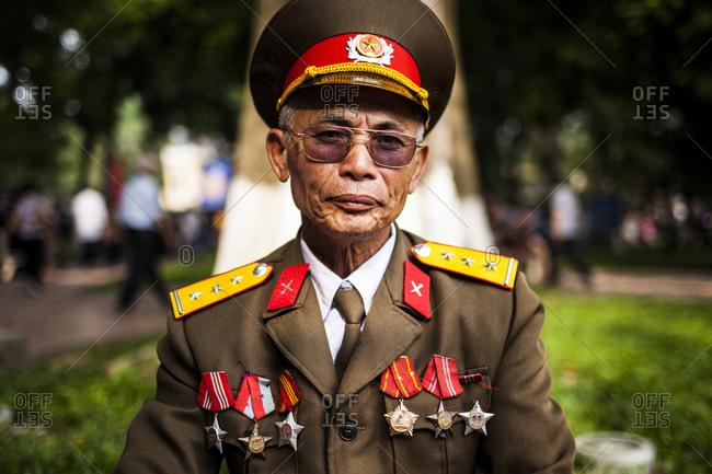 Hanoi, Vietnam - October 1, 2010: Portrait of a retired soldier sitting at Hoan Kiem lake in downtown Hanoi, Vietnam.