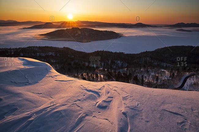 Sunset over a snowy landscape in Hokkaido, Japan